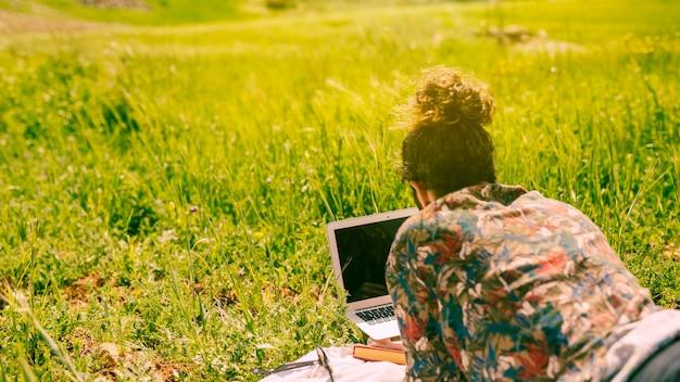Hombre mirando en la computadora portátil en la naturaleza
