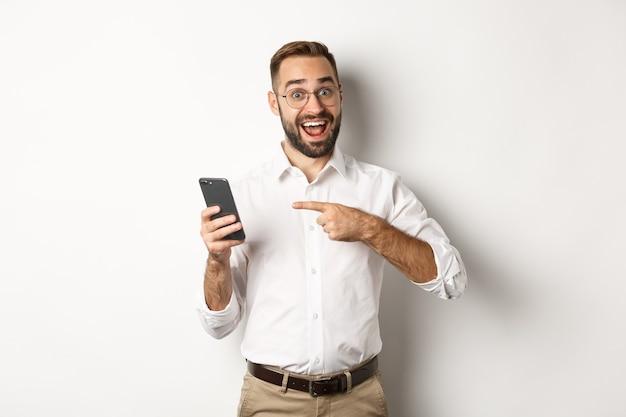 Hombre mirando emocionado y señalando con el dedo al teléfono móvil, mostrando una buena oferta en línea, de pie.