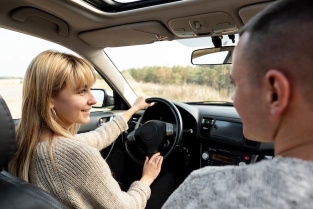 Hombre mirando hermosa esposa conduciendo