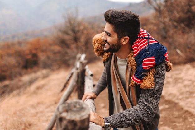 Hombre mirando hermosa vista y sosteniendo caniche sobre sus hombros. tiempo de otoño, vista lateral.