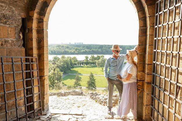 Hombre mirando a una mujer apoyada contra una pared.