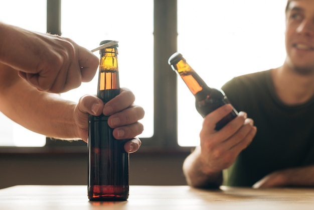 Un hombre mirando a una persona abriendo una botella de cerveza marrón en un restaurante