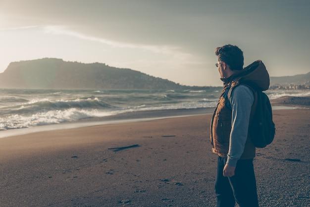 Hombre mirando la playa de sein durante el día y mirando pensativo