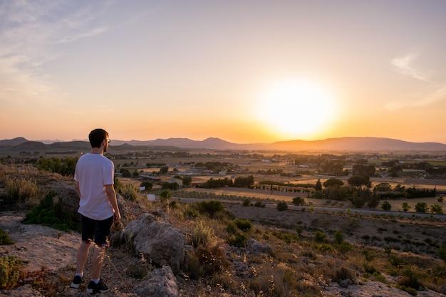 Hombre mirando la puesta de sol en una montaña