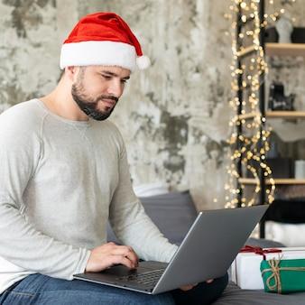 Hombre mirando su computadora portátil el día de navidad
