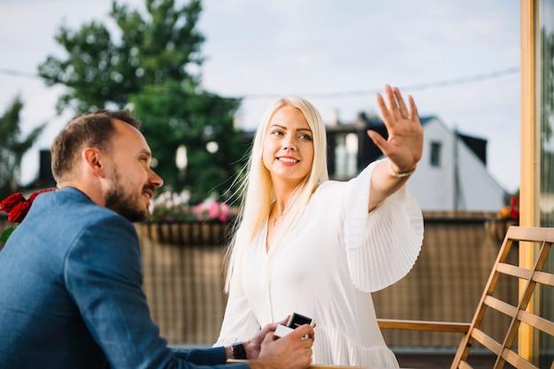 Hombre mirando a su novia mostrando el anillo de compromiso