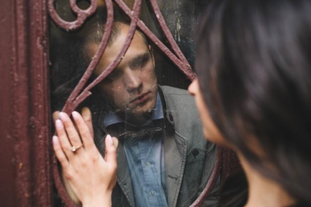 Hombre mirando a su novia a través de un cristal Foto gratis