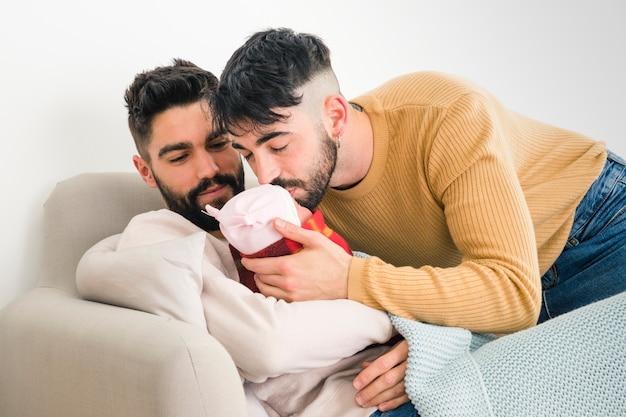 Hombre mirando a su novio besando a su bebé durmiendo