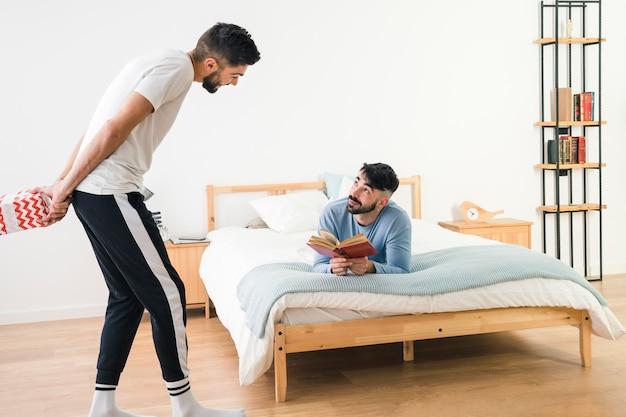 Hombre mirando a su novio de pie y sosteniendo una caja de regalo detrás de su espalda