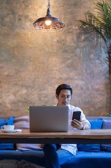Hombre mirando el teléfono celular mientras trabajaba en la computadora portátil en la cafetería.