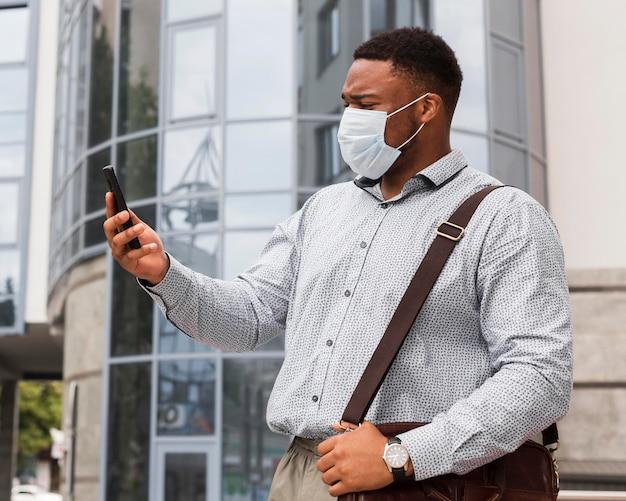 Hombre mirando el teléfono inteligente en su camino al trabajo mientras usa máscara