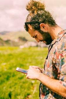 Hombre mirando el teléfono móvil en el campo