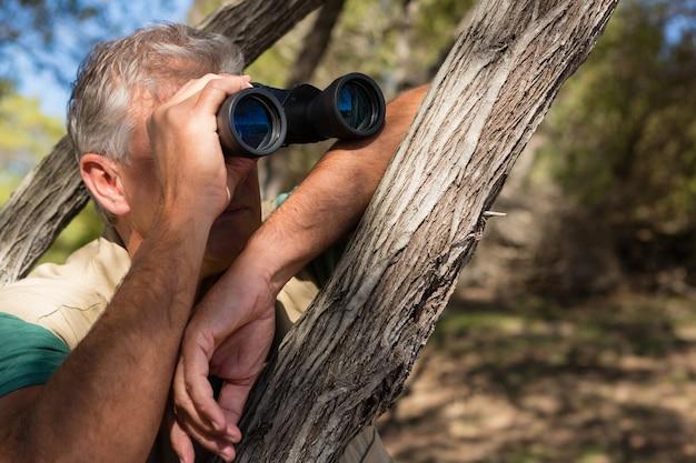 Hombre mirando a través de binoculares por árbol
