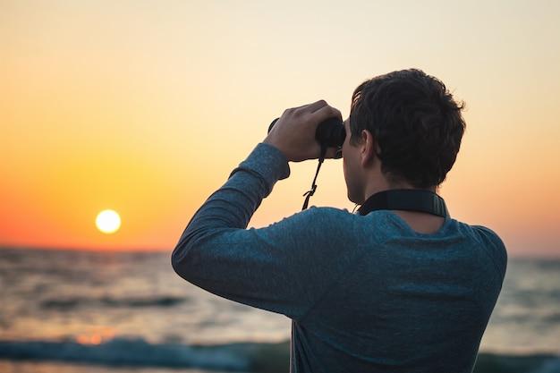 Un hombre mirando a través de binoculares de pie en la playa.