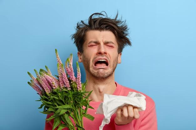 Hombre miserable en depresión sufre de malestar alérgico y rinitis, enfermedad estacional, cansado de estornudar, tiene la nariz y los ojos enrojecidos, alergia a la floración, sostiene un pañuelo, siente irritación