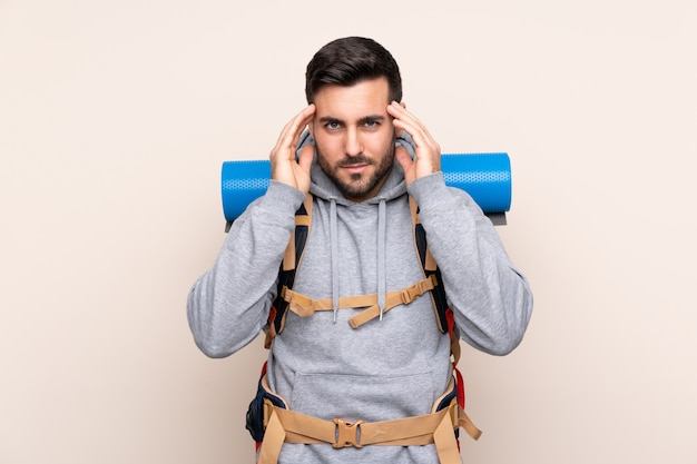 Hombre con mochila de alpinista sobre pared aislada