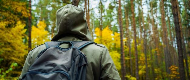 Un hombre con mochila camina en el increíble bosque de otoño.