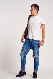 Un hombre con una mochila en la espalda en jeans, camiseta, zapatillas de deporte de cuerpo entero y gafas en la cara.