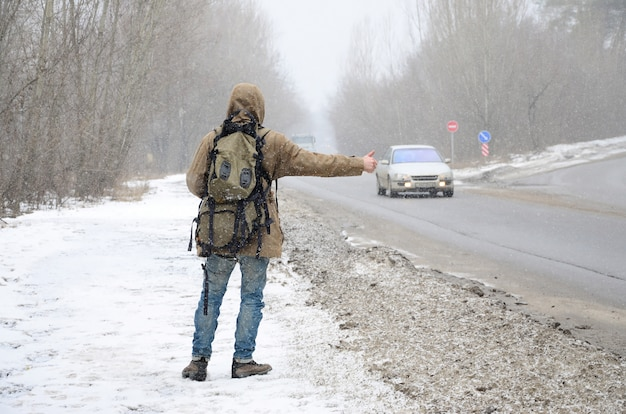 Un hombre con una mochila grande que muestra los pulgares para hacer autostop.