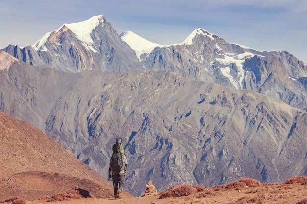 Un hombre con una mochila y una guitarra va de camino a las montañas de nepal. vista trasera.