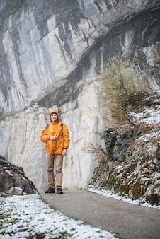 Hombre con mochila de senderismo en las montañas rocosas de niebla