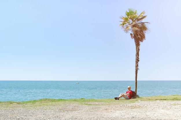 Hombre con mochila se sienta bajo una palmera alta en el fondo del mar y el cielo azul