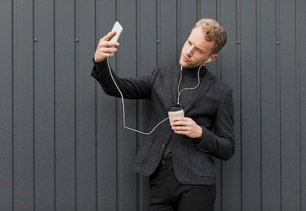 Hombre de moda con café tomando una selfie