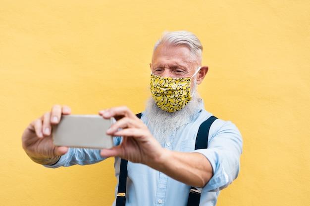 Hombre de moda hipster usando teléfono móvil haciendo videollamadas mientras usa máscara de seguridad de seda de moda