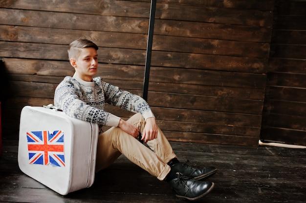 Hombre de moda joven con una maleta con la bandera británica
