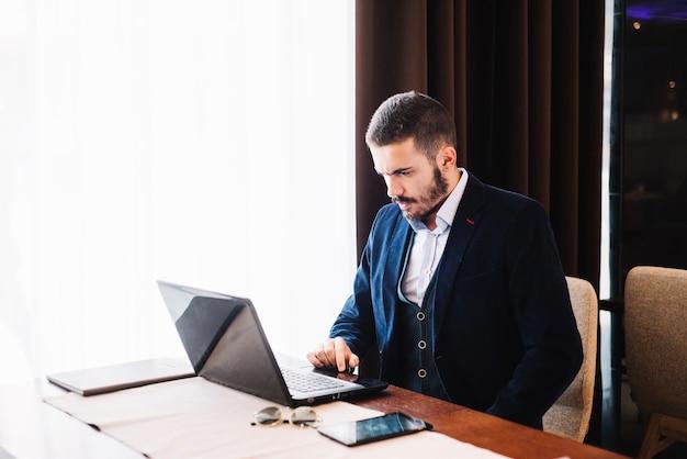 Hombre de moda en la mesa con gadgets