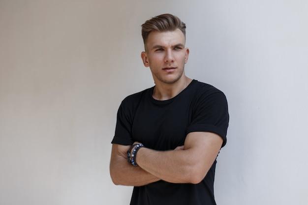 Hombre de moda modelo americano guapo con peinado en camiseta negra de moda cerca de la pared blanca