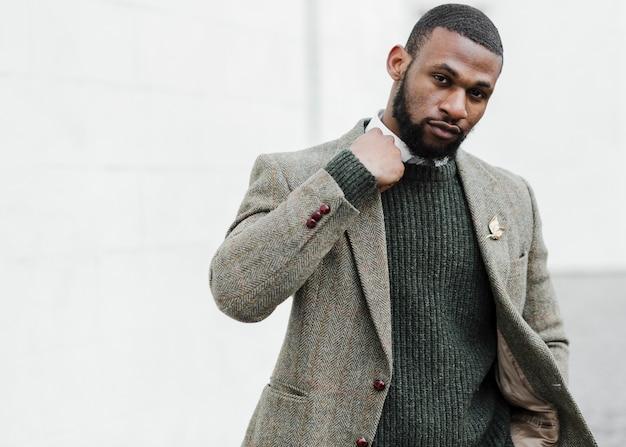 Hombre de moda posando afuera con espacio de copia