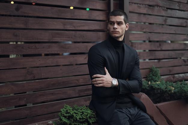 Hombre de moda, vestido con traje, sentado contra la pared de madera