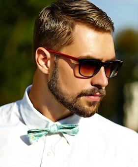 Hombre modelo guapo hipster en ropa de verano elegante posando en gafas de sol