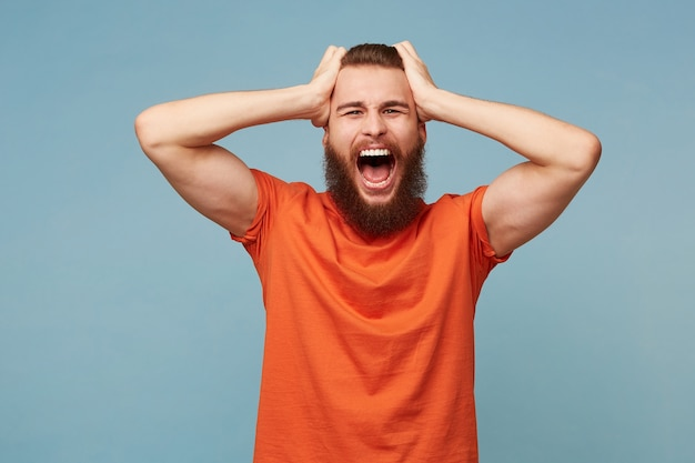 Hombre modelo sosteniendo su cabeza con las manos grita en voz alta, expresión facial de ira, aislada en azul.