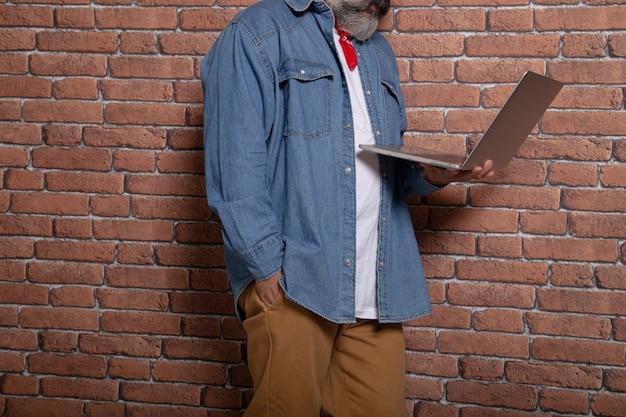 El hombre moderno apoyado en la pared de ladrillo tiene una computadora portátil. espacio de trabajo conjunto