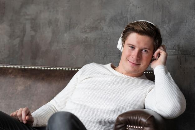 Hombre moderno escuchando música con auriculares mientras está sentado