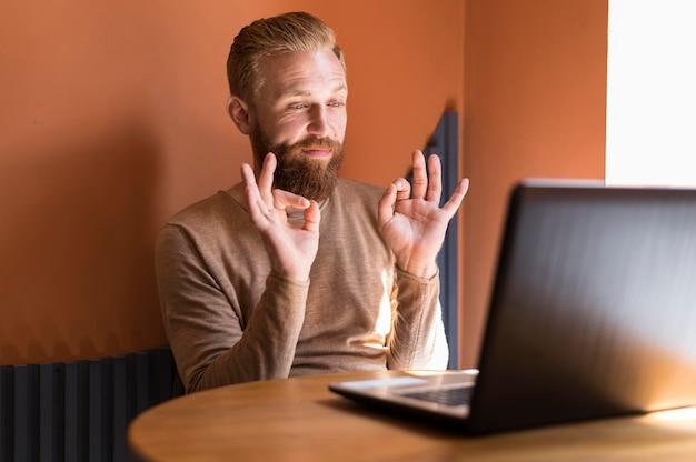 Hombre moderno guapo con una videollamada de trabajo