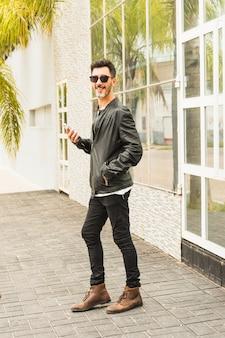 Hombre moderno con las manos en su bolsillo sosteniendo teléfono inteligente de pie delante de la puerta