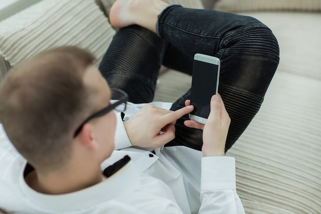 Hombre moderno mirando a través de un texto en su teléfono inteligente. personas y tecnologia