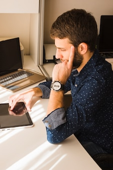 Hombre moderno pensativo que usa la tableta digital