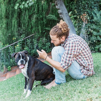 Hombre moderno con perro en jardín