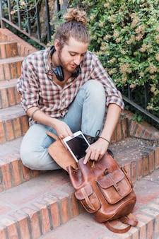 Hombre moderno poniendo tableta en mochila