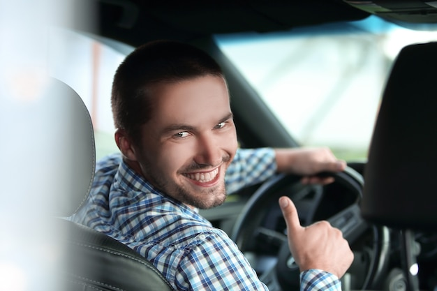 Hombre moderno sentado en un coche y mostrando su pulgar hacia arriba