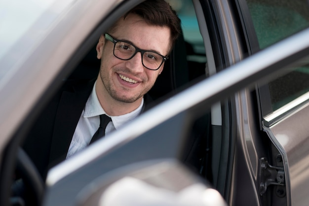Hombre moderno sonriente en coche