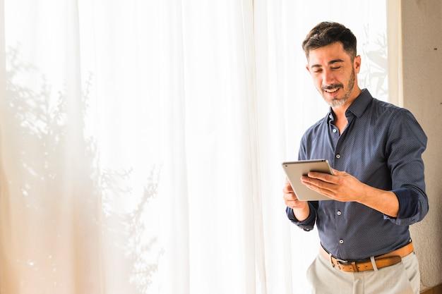 Hombre moderno sonriente que se coloca delante de la cortina blanca usando la tableta digital