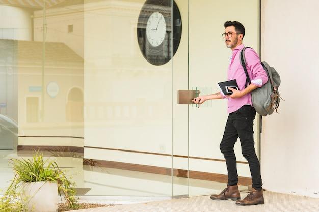 Hombre moderno con su mochila con diario y teléfono móvil de pie en la entrada de la puerta de vidrio