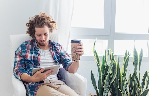 Hombre moderno con tableta en sofá