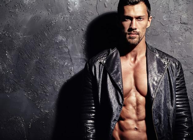 Hombre mojado guapo sobre fondo de pared negra