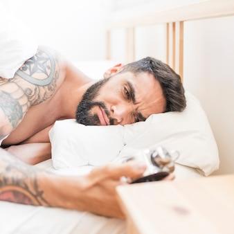 Hombre molesto acostado en la cama mirando el reloj de alarma